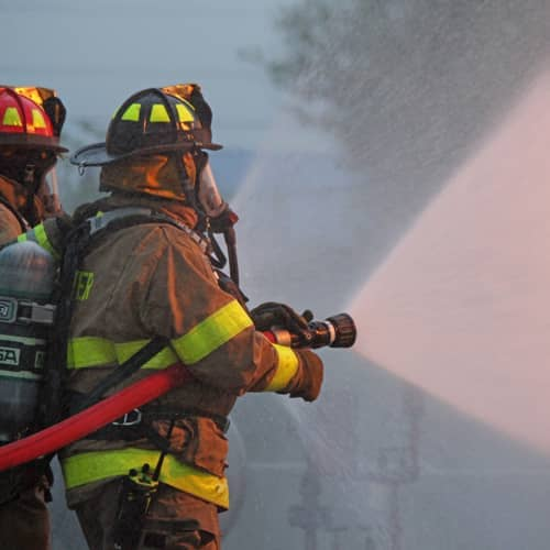Two firefighters using hoses to spray water