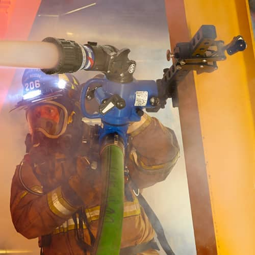 firefigter using TFT nozzle to fight a fire
